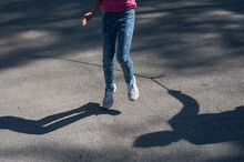Low Section Of Girl Jumping On Road