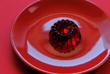 Red Jelly Dessert In A Red Round Plate On A  Red Background . A Gelatinous Dietary Low Calorie Vegetarian Dessert. Vegan Dessert. Low Calorie Diet Sweets