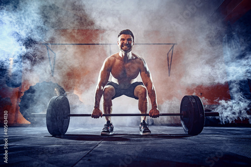 Obraz Muscular fitness man doing deadlift a barbell over his head in modern fitness center. Functional training. Snatch exercise. Smoke on background. - fototapety do salonu