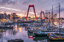 Rotterdam, The Netherlands, January 13, 2021: Historic Barges In The Old Harbour With In The Background The Illuminated Pylons Of Willems Bridge Under A Dramatic Sky At Sunrise