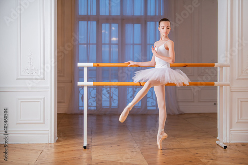 Canvastavla young slender ballerina in a white tutu standing on pointe at ballet bar in a beautiful white hall in front of a mirror