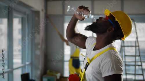 Fotografiet Tired african american construction worker drinking water