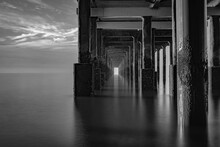 Reflection Of Bridge In Sea Against Sky
