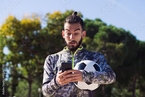 Fototapeta trendy sportsman consulting his mobile phone