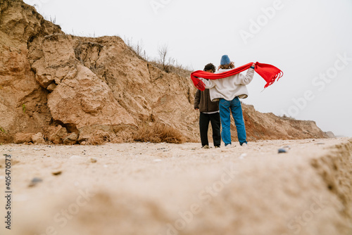 Canvas Print Attractive young multiethnic couple walking at the beachside