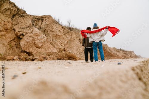 Slika na platnu Attractive young multiethnic couple walking at the beachside
