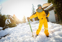 Teenage Girl Clearing Snow With Shovel