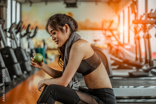 Side View Of Smiling Woman Holding Granny Smith Apple While Sitting In Gym Poster Mural XXL