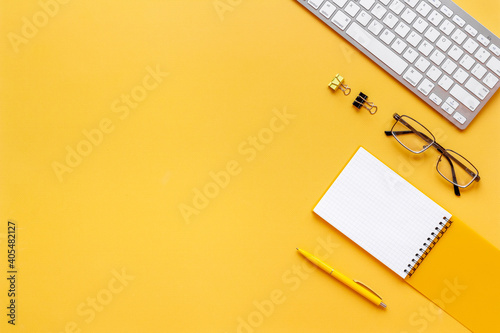 Yellow flat lay top view office table desk with keyboard and office supplies - fototapety na wymiar