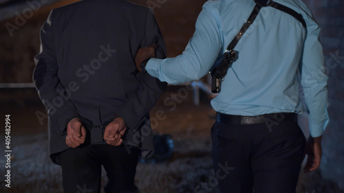 Canvas Back view pf police officer leading criminal in handcuffs at crime scene
