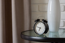 On The Coffee Table There Is An Alarm Clock And Shows The Morning Time At Twelve Minutes To Seven