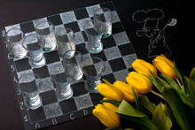 Chessboard With Glasses And A Bouquet Of Yellow Tulips. March 8 And Valentine's Day Gift