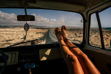 Travel And Freedom Concept People With Close Up Of Woman Legs Enjoy The Road Trip Inside An Old Vintage Van - Vanlife Lifestyle Girl With Long Road Asphalt In Background