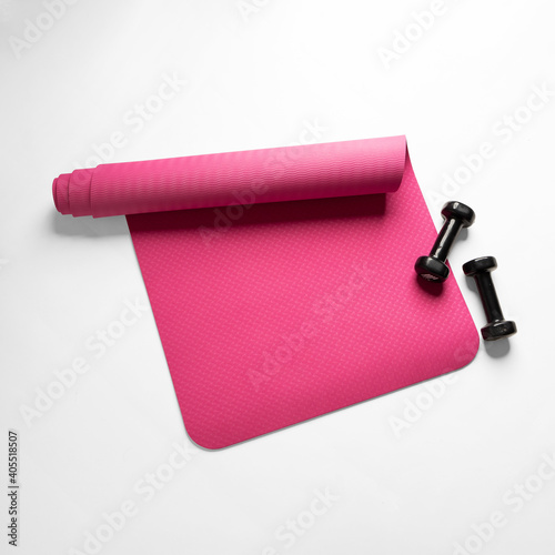 Obraz Top view of a pink fitness mat and two black dumbbells isolated on a white background - fototapety do salonu