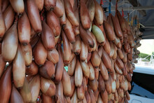 Bunches Of Orange Onions Hanging On The Rail For Sale In Food Market