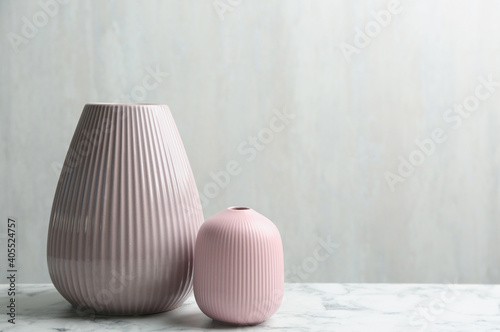Photo Stylish pink ceramic vases on white marble table, space for text