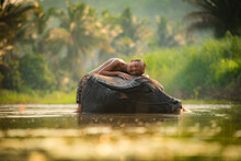 Smiling Boy Sleeping On Water Buffalo In Lake