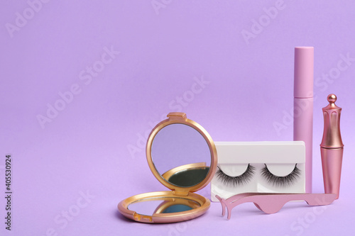 Obraz Magnetic eyelashes and accessories on violet background. Space for text - fototapety do salonu