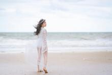 Beautiful Women In White Dress Happily Strolling At The Beach, Beautiful Woman Dressed In White Bride