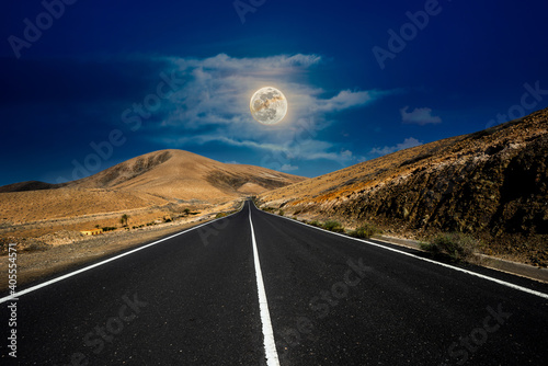 Asphalt road in the mountains with the moon in the sky