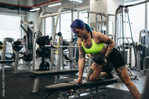 Fototapeta premium tattooed woman training in gym