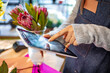 canvas print picture - Young girl takes pictures of floral bouquets on a tablet. Beautiful female florist with tablet in flower shopv. Mid section portrait of unrecognizable florist using digital tablet in shop