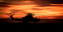 Silhouette Of An Attack Helicopter At Against A Dramatic Cloudy Sky At Sunset Or Sunrise