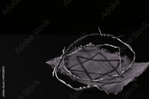 Fotografia, Obraz Fabric with star of David and barbed wire on black background, space for text