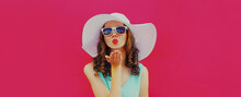 Portrait Of Beautiful Young Woman Blowing Her Red Lips Sending Sweet Air Kiss Wearing A Summer Straw Hat On A Pink Background