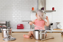 Funny Baby Boy Playing On Kitchen Counter With Colander Over His Head