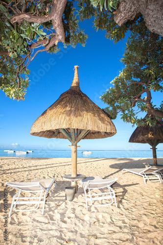 Tela straw sunshade and sunbeds at a tropical beach
