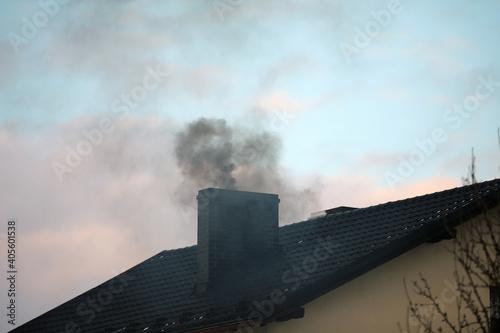 Fototapeta Dark smoke from a chimney from a single-family house