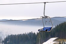 Empty Ski Lift Seats Going Down On Blurred Background Of Mountain Landscape In Fog