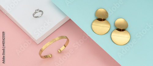 Fototapeta Flat lay of modern golden jewelries on pastel colors background