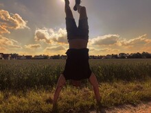 Man With Arms Raised Doing Handstand On Grass Against Sky During Sunset