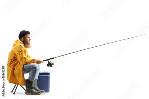 Fotografia, Obraz Profile shot of a bearded fisherman catching with a fishing pole seated on a cha
