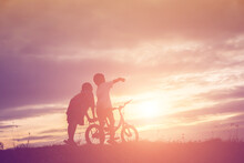Silhouette Friends Riding Bicycle On Land Against Sky At Sunset