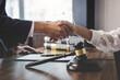 Leinwandbild Motiv Close-up Of Lawyer And Customer Shaking Hands On Table