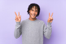 Young African American Man Isolated On Purple Background Showing Victory Sign With Both Hands