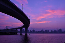 Bridge Over River In City At Sunset