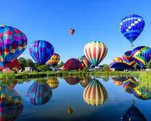 Hot Air Balloons Flying Over Lake Against Clear Blue Sky
