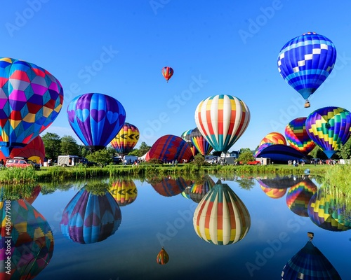 Fotografiet Hot Air Balloons Flying Over Lake Against Clear Blue Sky