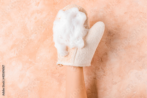 Photographie Female hand with massage glove on color background