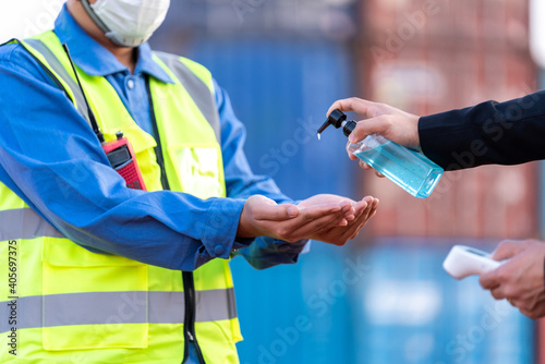 Fotografia Worker wash your hands with gel and scanning fever temperature with digital thermometer to industry construction site staff wearing hygiene face mask protect from Coronavirus or COVID-19