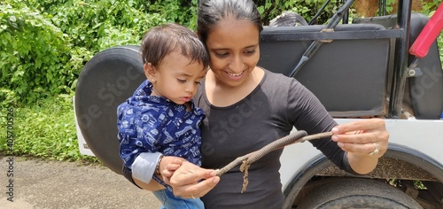 Mother And Son Looking At Centipede On Stick Against Vehicle Fototapete