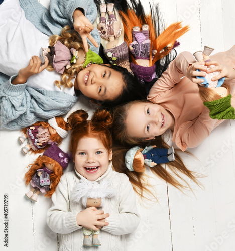 Fotografia, Obraz Three happy laughing international kids girls in warm sweaters are lying on white floor head to head with little doll toys in kindergarten