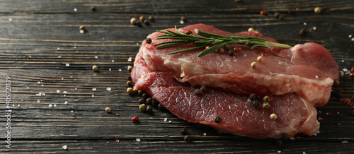 Fototapeta Fresh raw steak meat with herbs and spices on wooden background obraz
