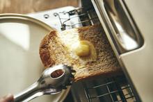 バターをのせた食パンをトースターから取り出す
