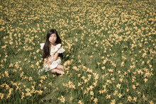 Girl Sitting Outside In Field Of Yellow Daffodils Flowers