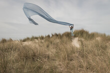 Girl In A Blue Dress Standing On Dune Holding And Flying A Large Blue Thin Drape In The Wind